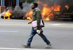 Baltimore burns man walks by