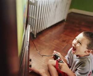 Boy (5-7) playing video game on television, elevated view